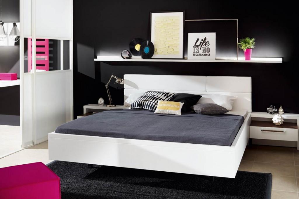 """Nebenan, im Schlafzimmer, setzt sich das Farbspiel Schwarz-Weiß-Pink fort. Kopfteil und Nachttischelemente mit Schublade machen das Bett zur komfortablen """"Relax-Zone""""."""